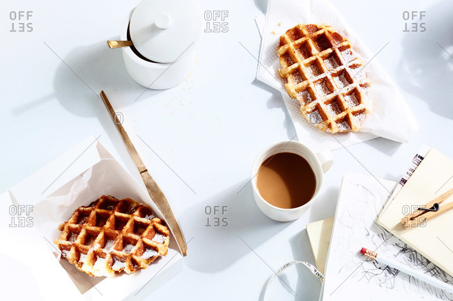 Liege waffles, coffee mug, sugar bowl and artist's sketch on white surface