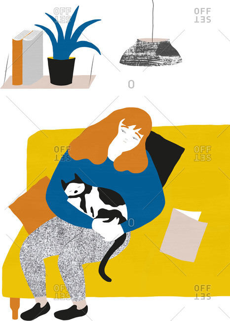Woman sitting on a couch holding a cat