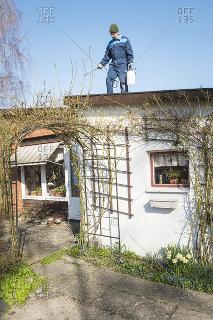 Man cleaning roof with a sprayer