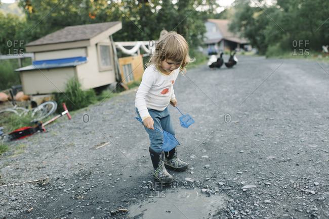 Girl playing in a driveway puddle