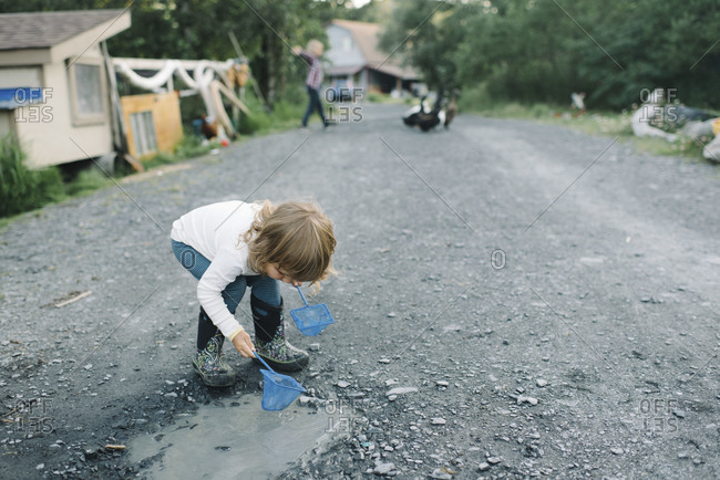 Girl playing in a puddle on a driveway