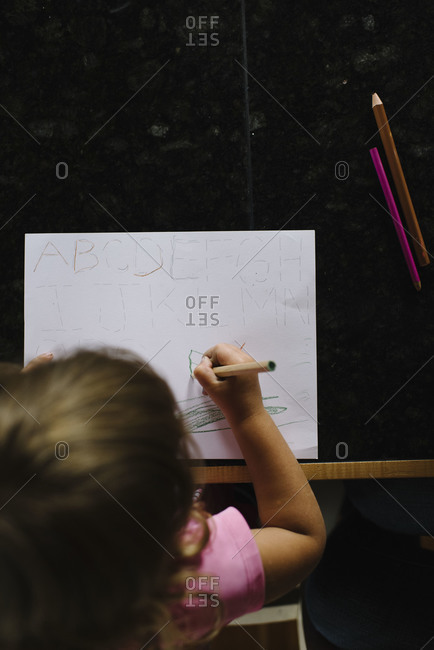 Girl practicing writing the alphabet