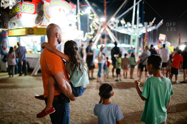 Family standing at a fairgrounds looking at rides