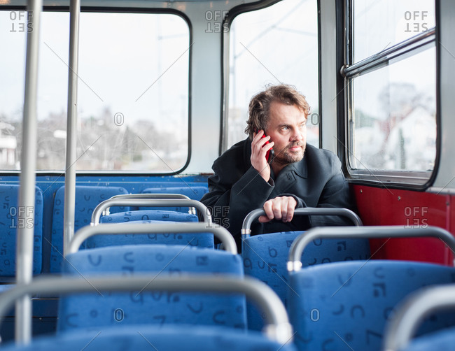 Man on a bus talking on a cellphone