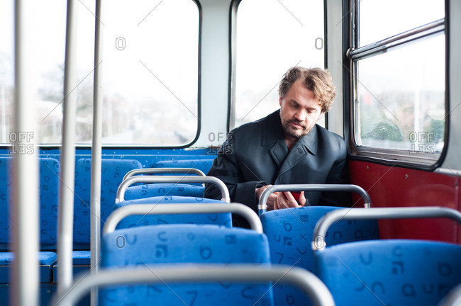 Man on a bus checking his phone