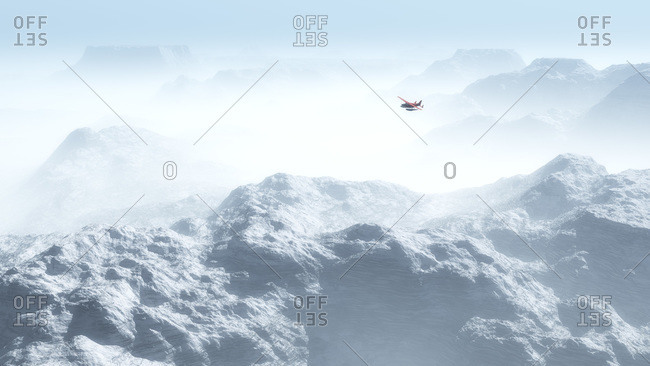 Plane flying above snow covered mountains