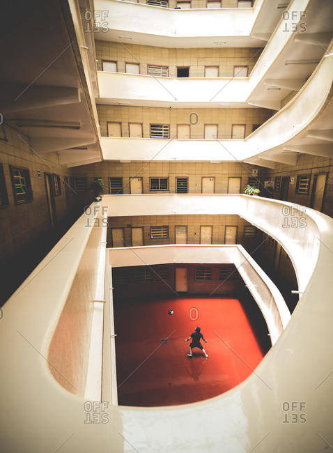 Man playing soccer in a building's atrium
