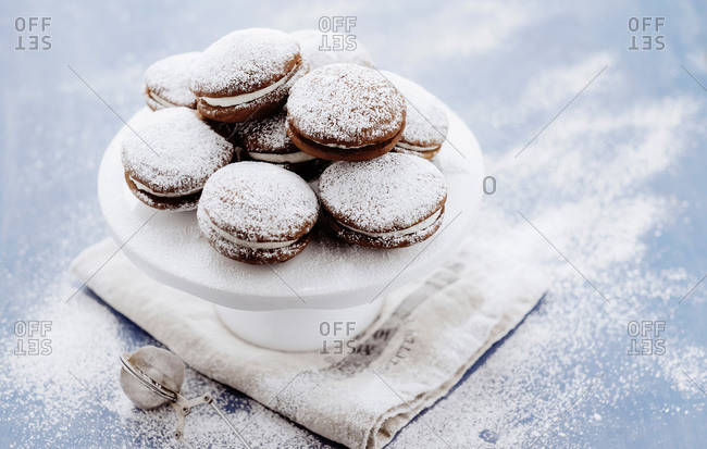 Cream-filled whoopie pies on cake stand dusted with powdered sugar