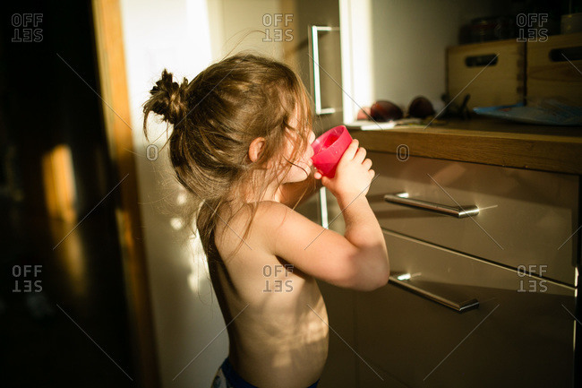 Girl drinking from a pink cup