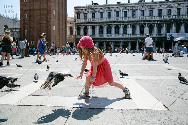 Girl chasing pigeons in St. Mark's Square in Venice, Italy