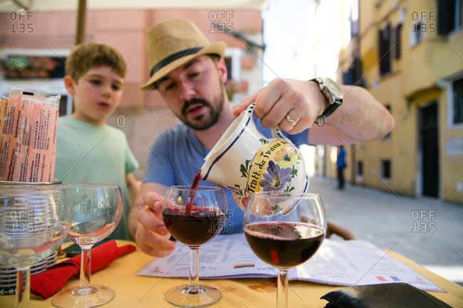 Boy watching wine being poured in Venice, Italy