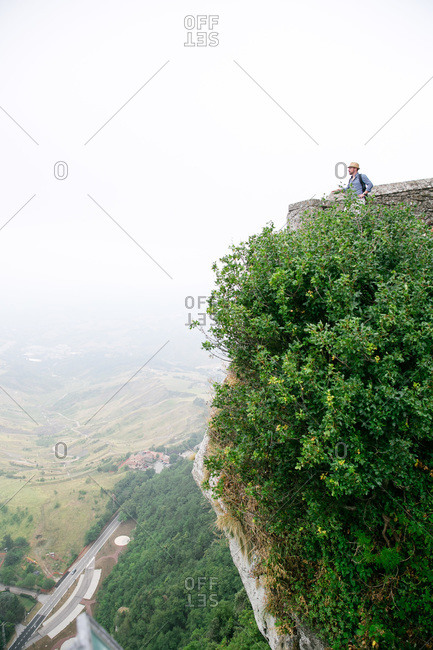 Tourist looking at view from castle in San Marino, Italy