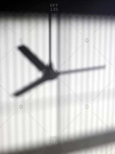 Shadow of ceiling fan on white wall