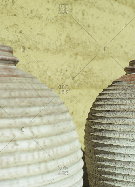 Detail of two earthenware pots against a stucco wall