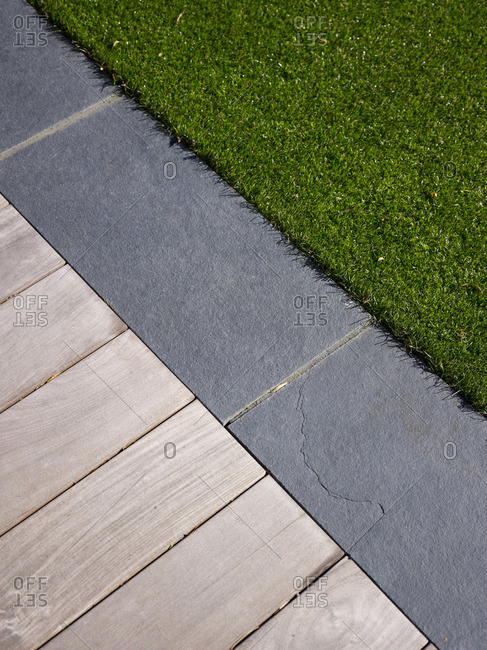 Closeup of grass, slate tiles, and wood decking, natural materials all used in a landscape design