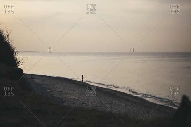 View to the beach with angler standing at seafront in the evening, Nienhagen