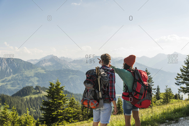 Young couple in alpine landscape looking at view, Tannheimer Tal