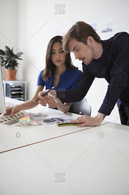 Young business colleagues discussing over swatches at desk
