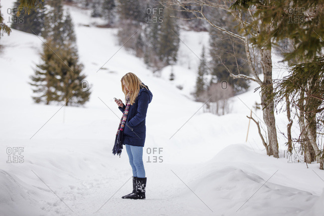 Young woman checking her smart phone in the winter