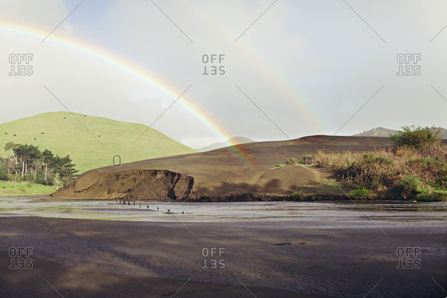Double rainbows over a hill