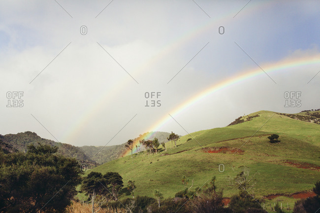 Double rainbows over a grassy hill
