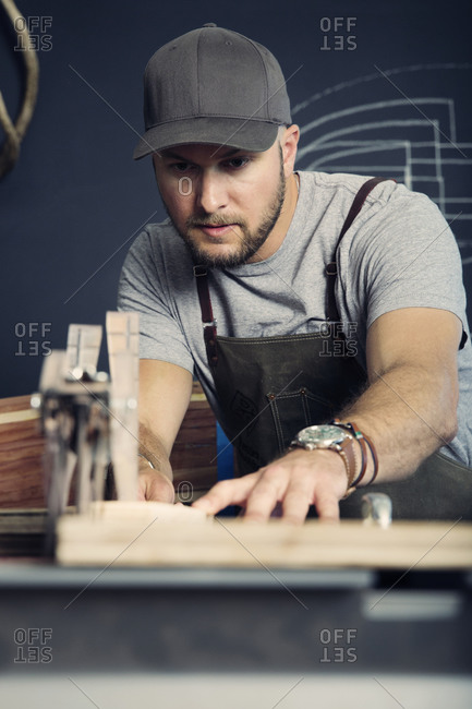 Man pushing a piece of wood over a table saw