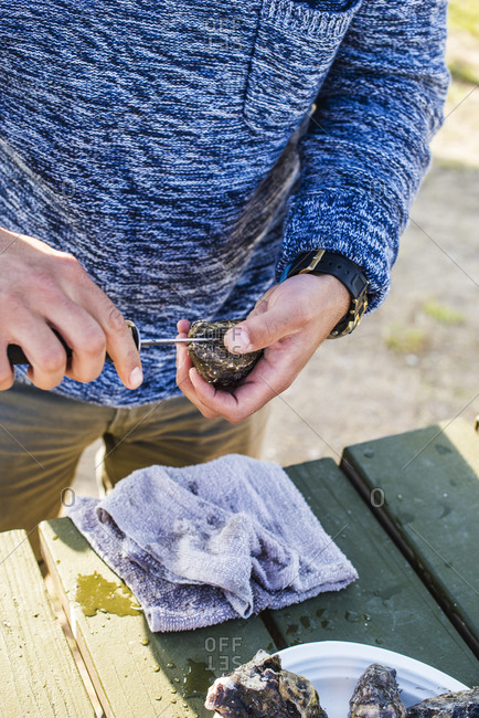 Man shucking oysters at a picnic table
