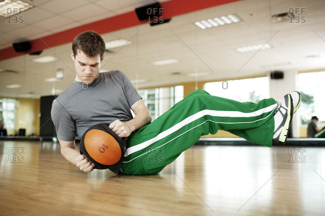 Man performing a twist crunch with a medicine ball