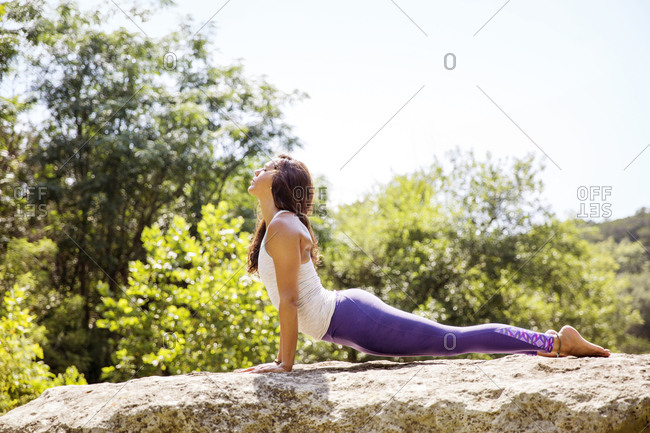 A young woman practices yoga on a rock in a forest