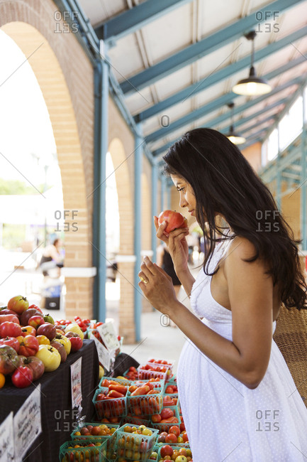 Pregnant woman sniffing a tomato at a farmers market