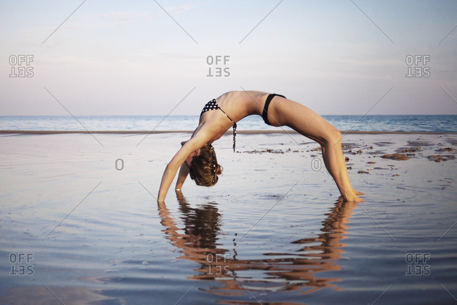 Woman bending in a yoga pose in a shallow tidal pool