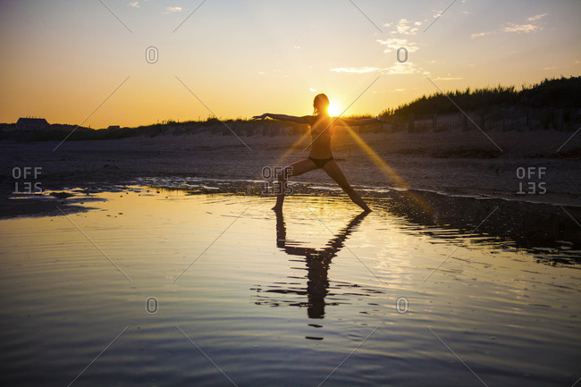 Woman in a warrior yoga pose on a beach