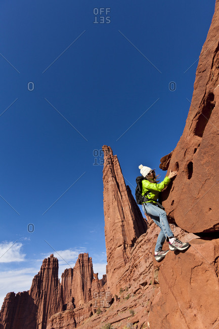 Woman climbing a sandstone spire in Canyonlands National Park