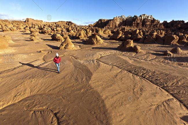 Woman walking across sandstone in Goblin Valley State Park, Utah