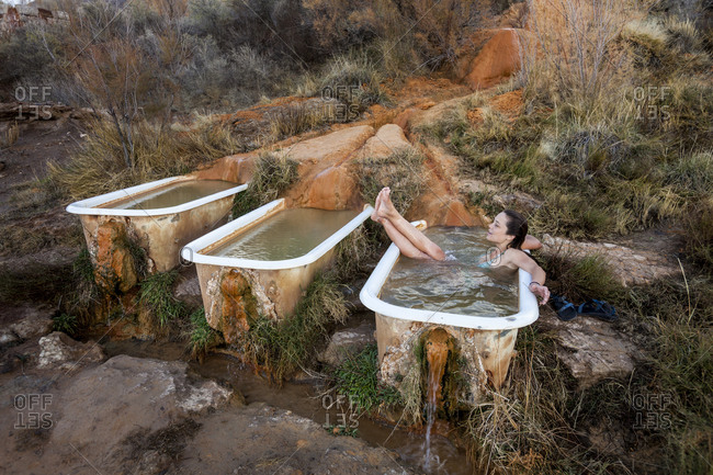 Woman relaxing in a tub fed by a hot spring