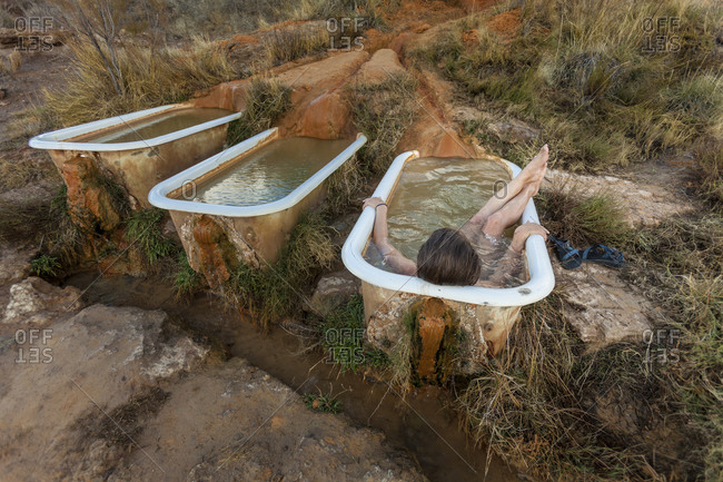 Woman lying down in a tub fed by a hot spring