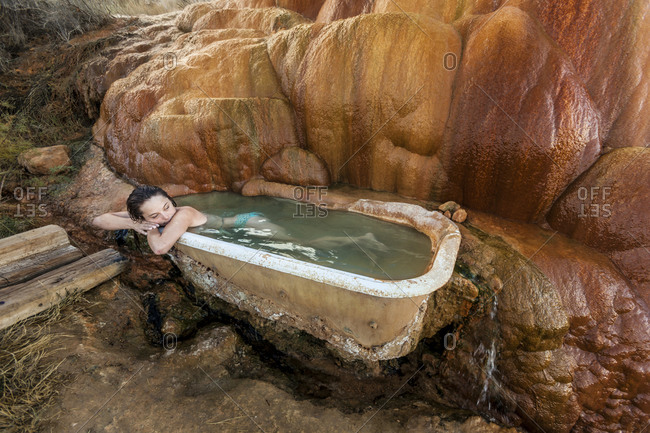Woman resting her head on the edge of a tub fed by a hot spring