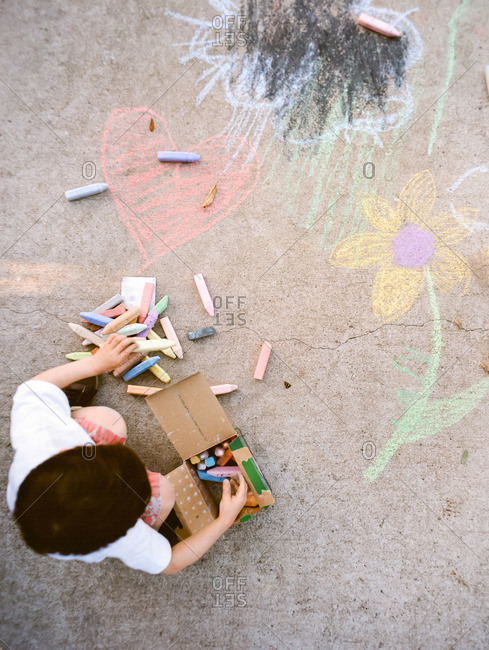 Overhead view of young boy drawing with sidewalk chalk