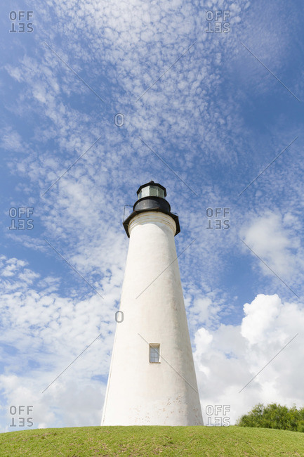 White lighthouse on a grassy hill against a blue sky with clouds