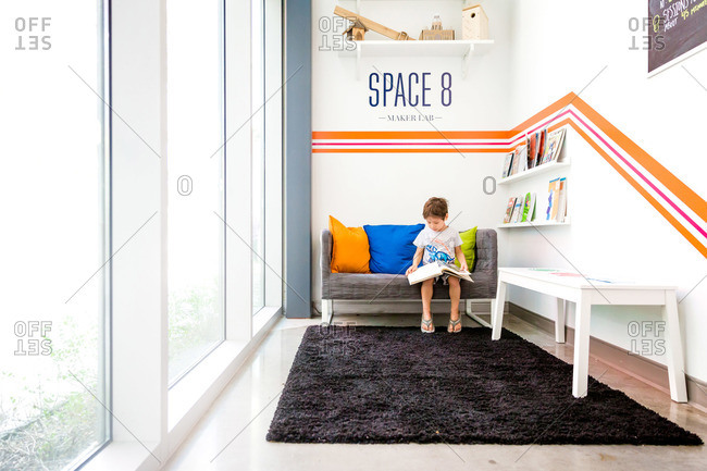 Boy reading a book in a science museum waiting area