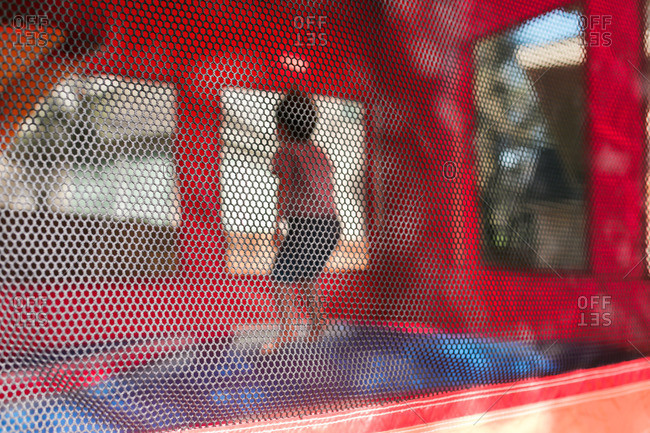 View through screen of child jumping in a bouncy house