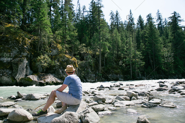 Man staring off sitting on river stones