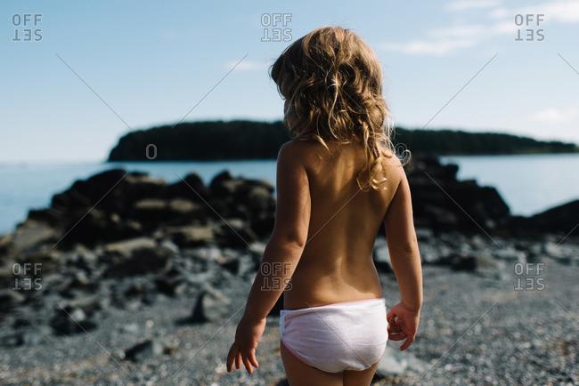 Little girl in underwear on rocky beach