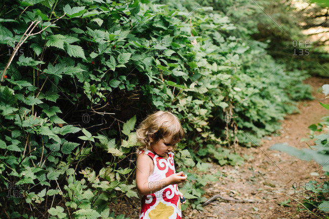 Girl in forest holding a picked berry