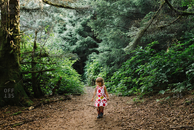 Little girl walking in forest clearing