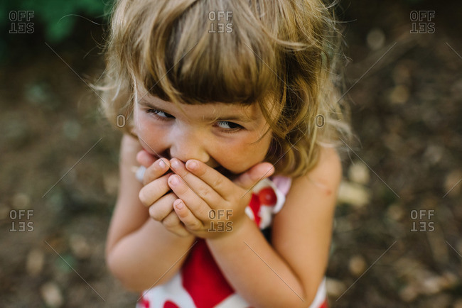 Girl covering mouth and giggling in forest