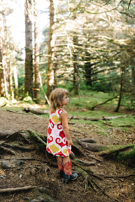 Girl in dress standing in a forest