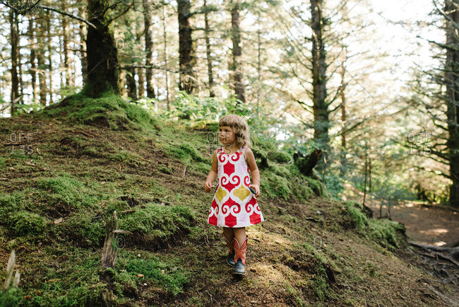 Girl walking through forest in cowboy boots