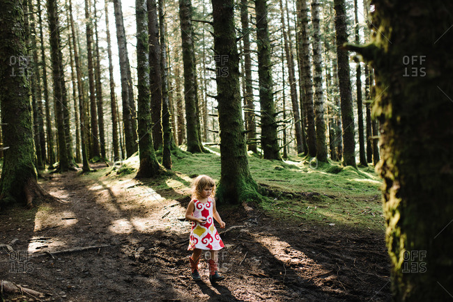 Girl in cowboy boots walking through forest