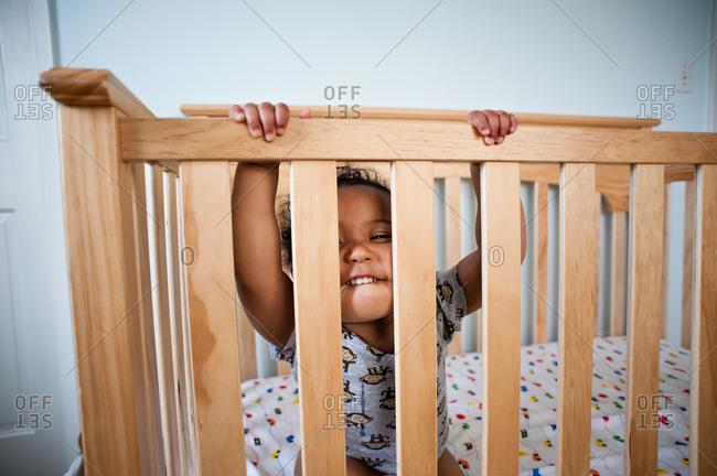 Toddler boy making goofy face in crib